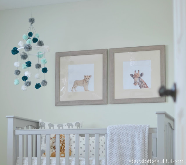 A DIY pom-pom mobile made from yarn and an embroidery hoop is a fun and stimulating addition to your little one's nursery. Find the full tutorial at www.aburstofbeautiful.com | A Burst of Beautiful