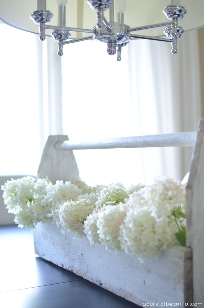 A vintage wood toolbox filled with white hydrangeas is the perfect summer centre-piece for your dining table | A Burst of Beautiful