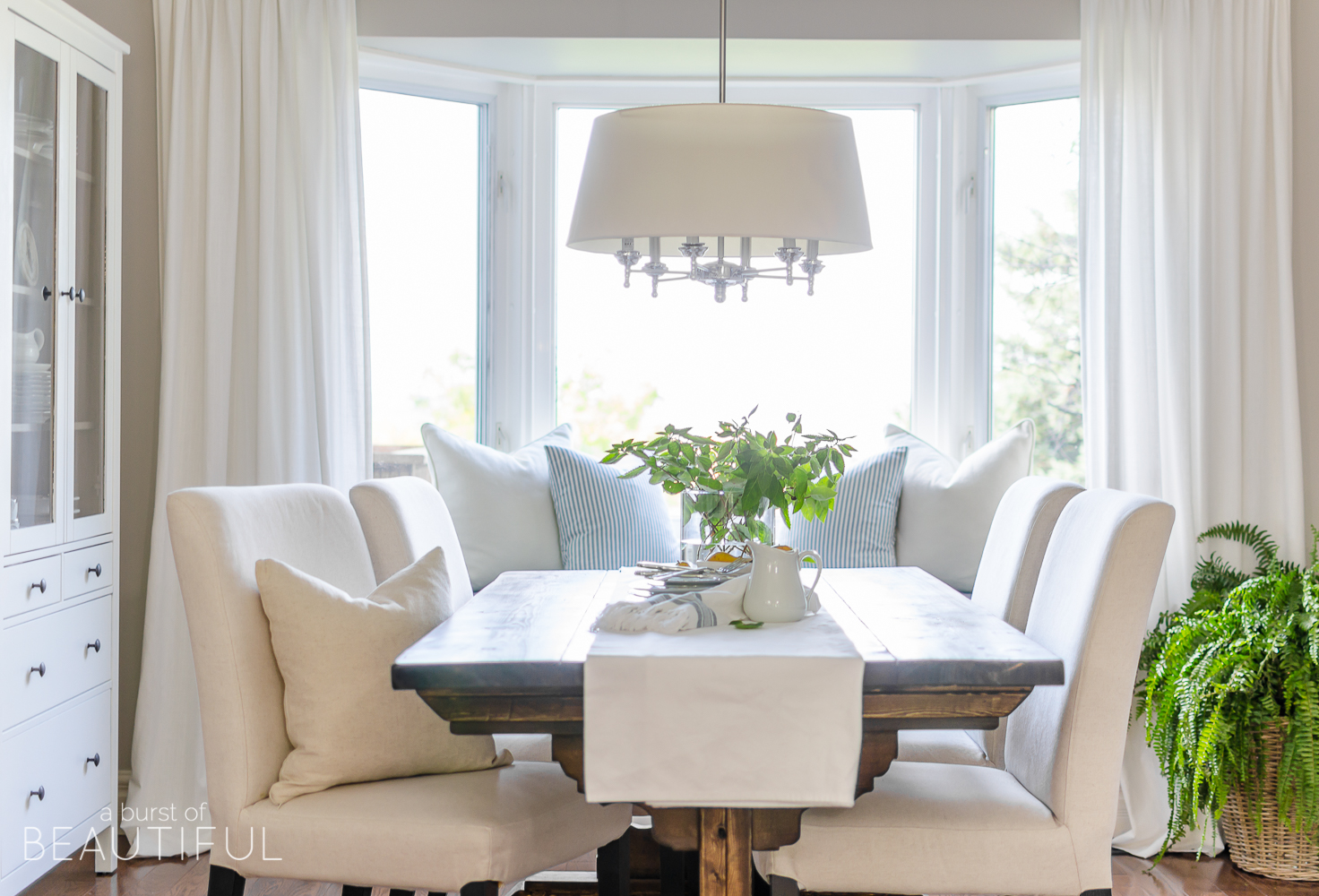 A DIY farmhouse dining table and window bench take center stage in this modern farmhouse dining room.
