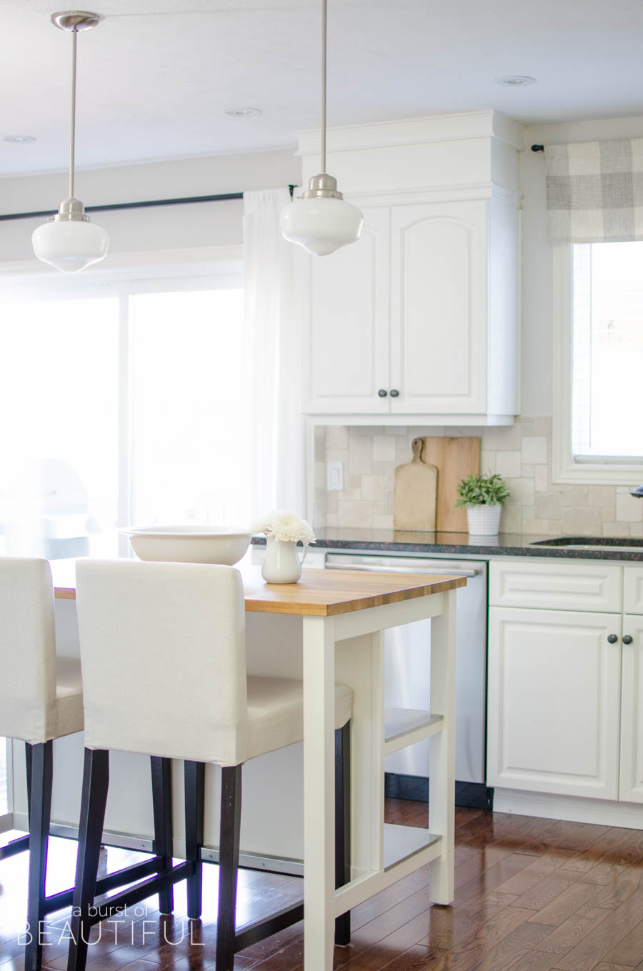 This simple farmhouse kitchen is the heart of this busy family's home. White cabinets, black granite counters and natural wood elements add plenty of texture and charm to this bright and airy space.