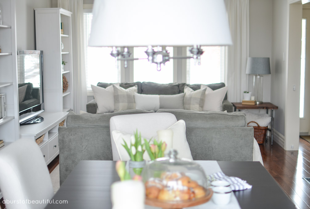 An assortment of grey and white pillows create a soft and inviting atmosphere in this modern farmhouse living room | A Burst of Beautiful