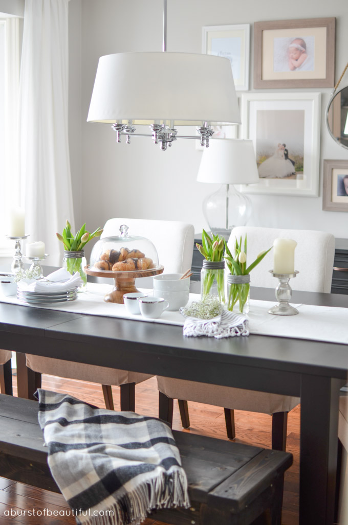 An open-concept dining room and living room is bright and inviting with a large farmhouse table, grey couch and eclectic gallery wall | A Burst of Beautiful