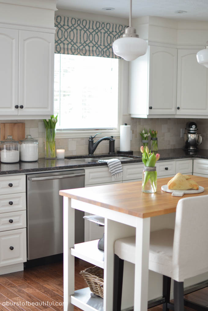 Beautiful white farmhouse kitchen, complete with butch block island, custom cabinetry and schoolhouse pendant lights | A Burst of Beautiful