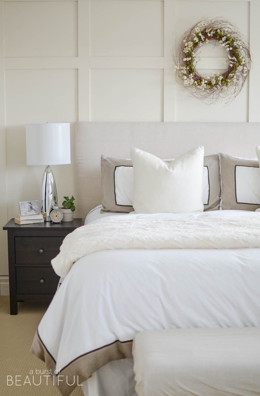 A Neutral Farmhouse Bedroom Welcomes Spring With Classic White Bedding, A  Grey Wingback Chair And
