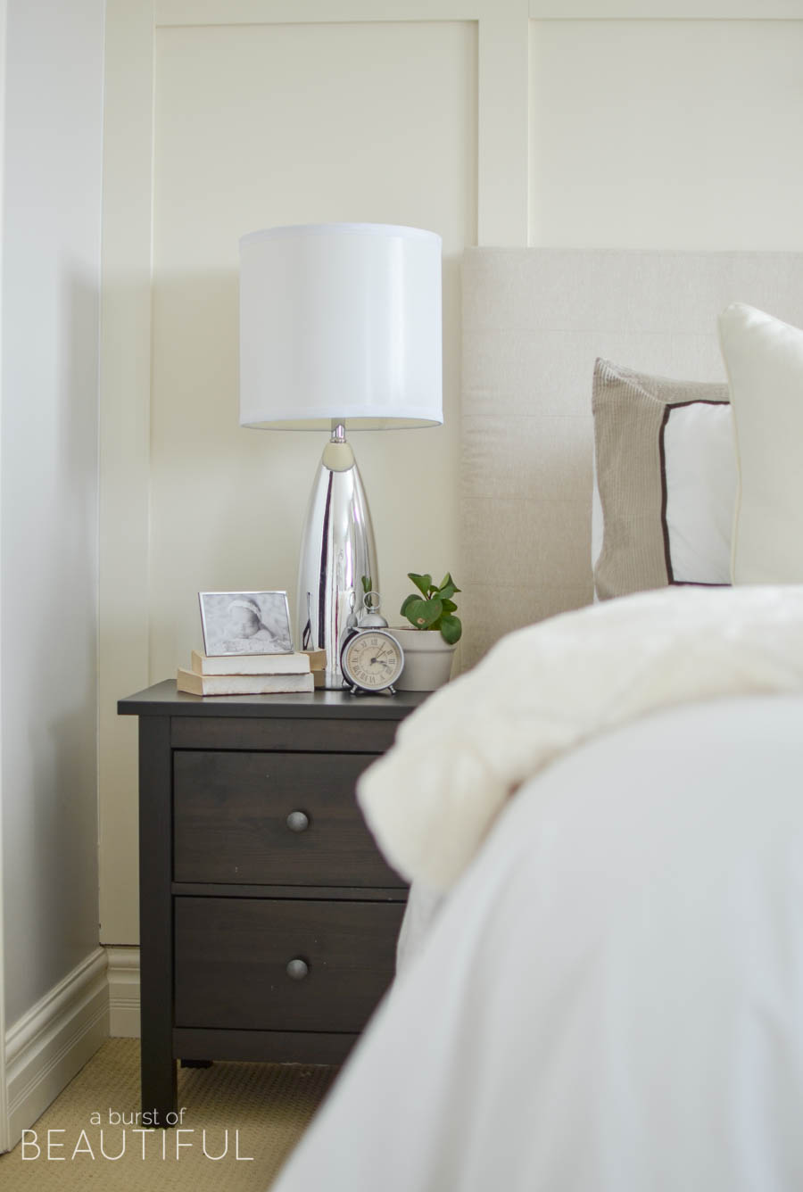 A neutral farmhouse bedroom welcomes spring with classic white bedding, a grey wingback chair and subtle pops of color | A Burst of Beautiful