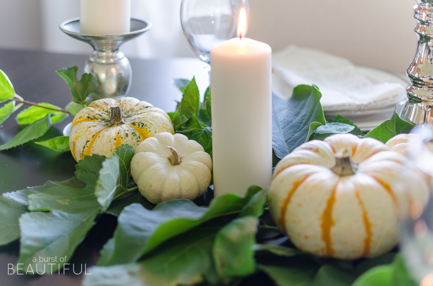 Create a simple and classic fall tablescape using mini pumpkins, fresh greenery and candles.