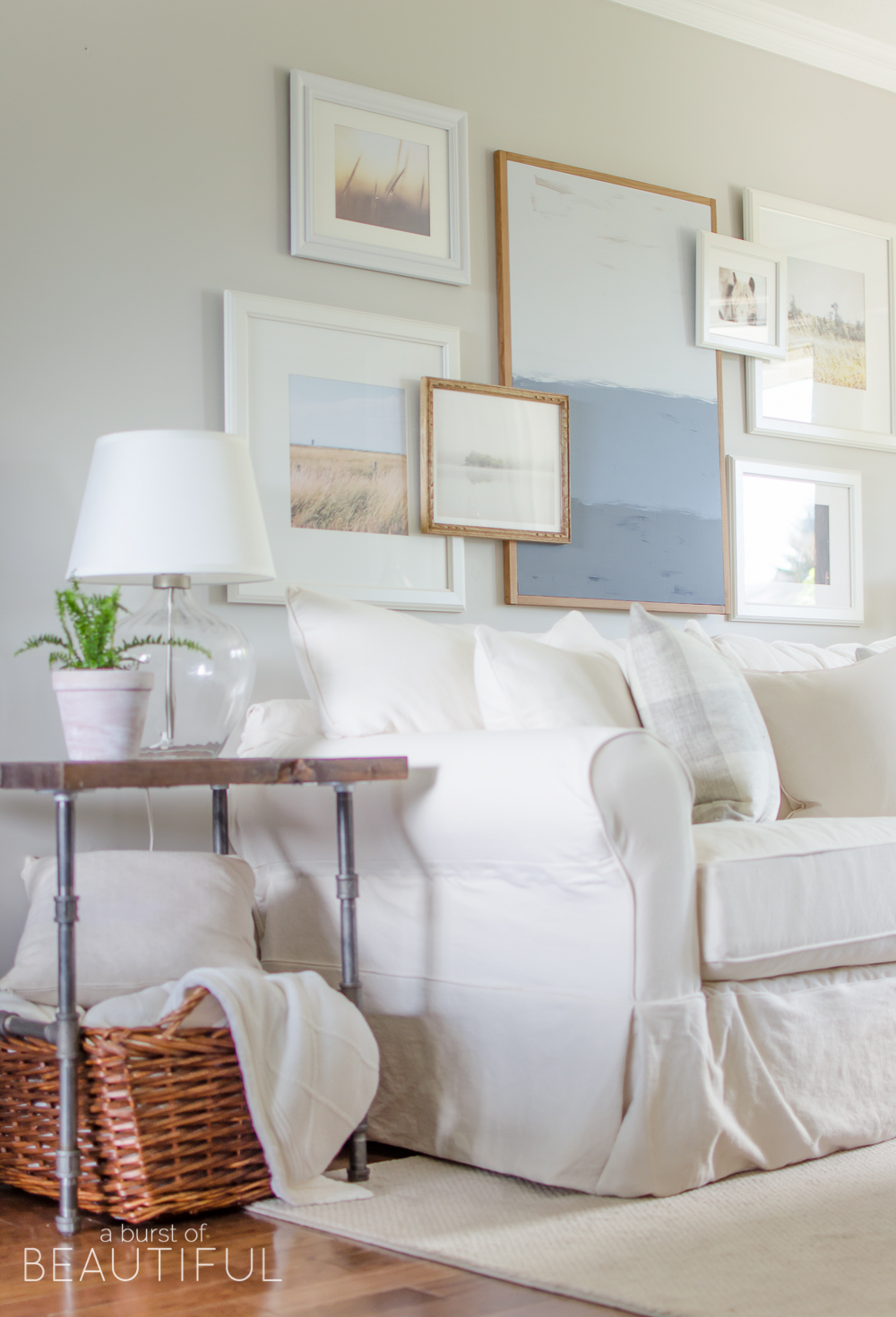 A white slipcovered sofa looks casual and relaxed in this charming farmhouse living room. Learn how to keep white slipcovered furniture clean at aburstofbeautiful.com.