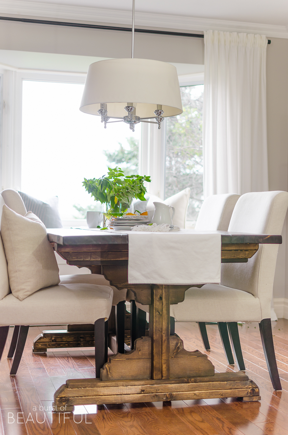 A bright and inviting dining room boasts simple farmhouse style with a DIY farmhouse dining table and classic window bench.