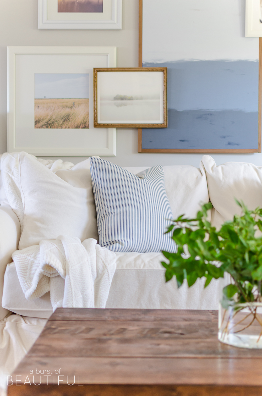 A layered gallery wall adds interest and depth to this charming modern farmhouse living room.