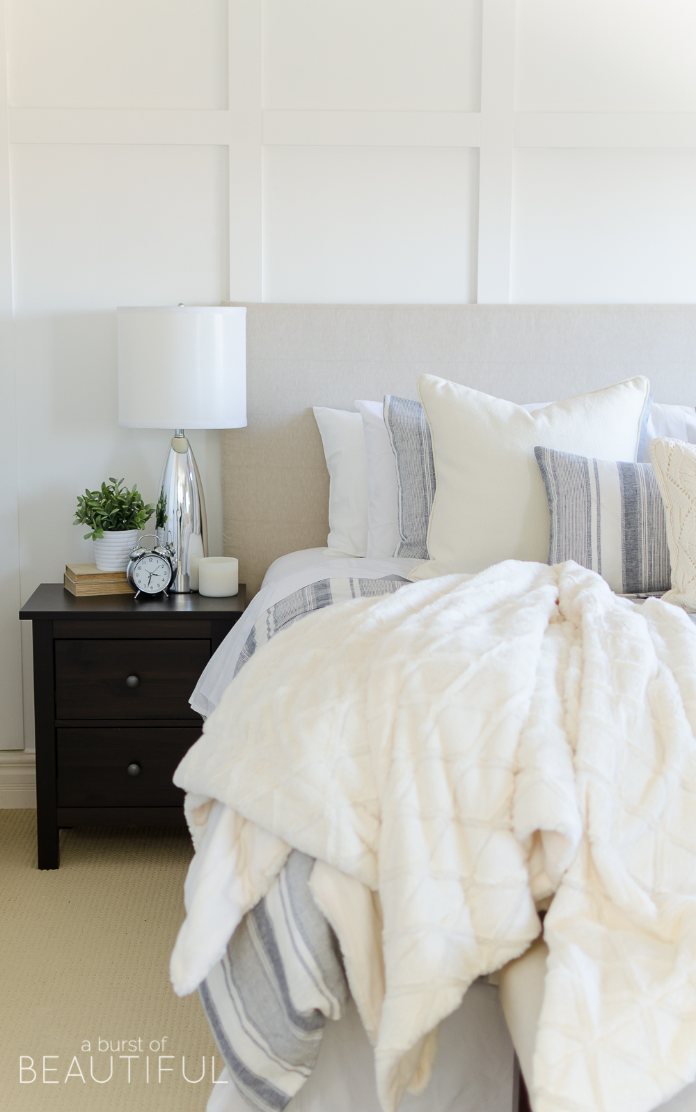 This cozy farmhouse master bedroom features a beautiful DIY shiplap fireplace, indigo ticking strip bedding and woven wood shades.