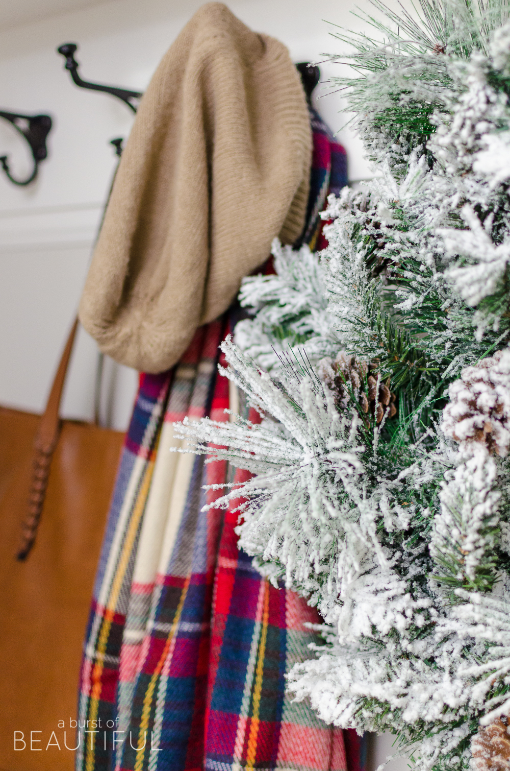A simple Christmas entryway receives a dose of holiday charm with a flocked wreath, velvet pillows and packages wrapped in festive Christmas paper.
