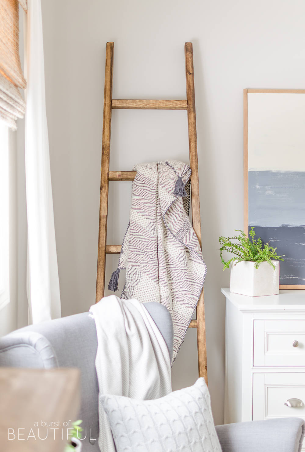 A simple DIY angled blanket ladder adds a touch of farmhouse charm to this cozy bedroom.