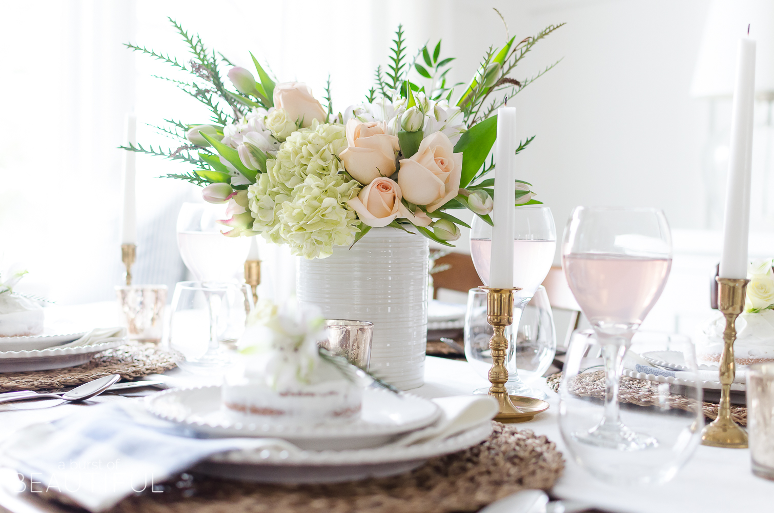 Roses, tulips and hydrangeas create the perfect centerpiece for this simple pink and gold spring tablescape.