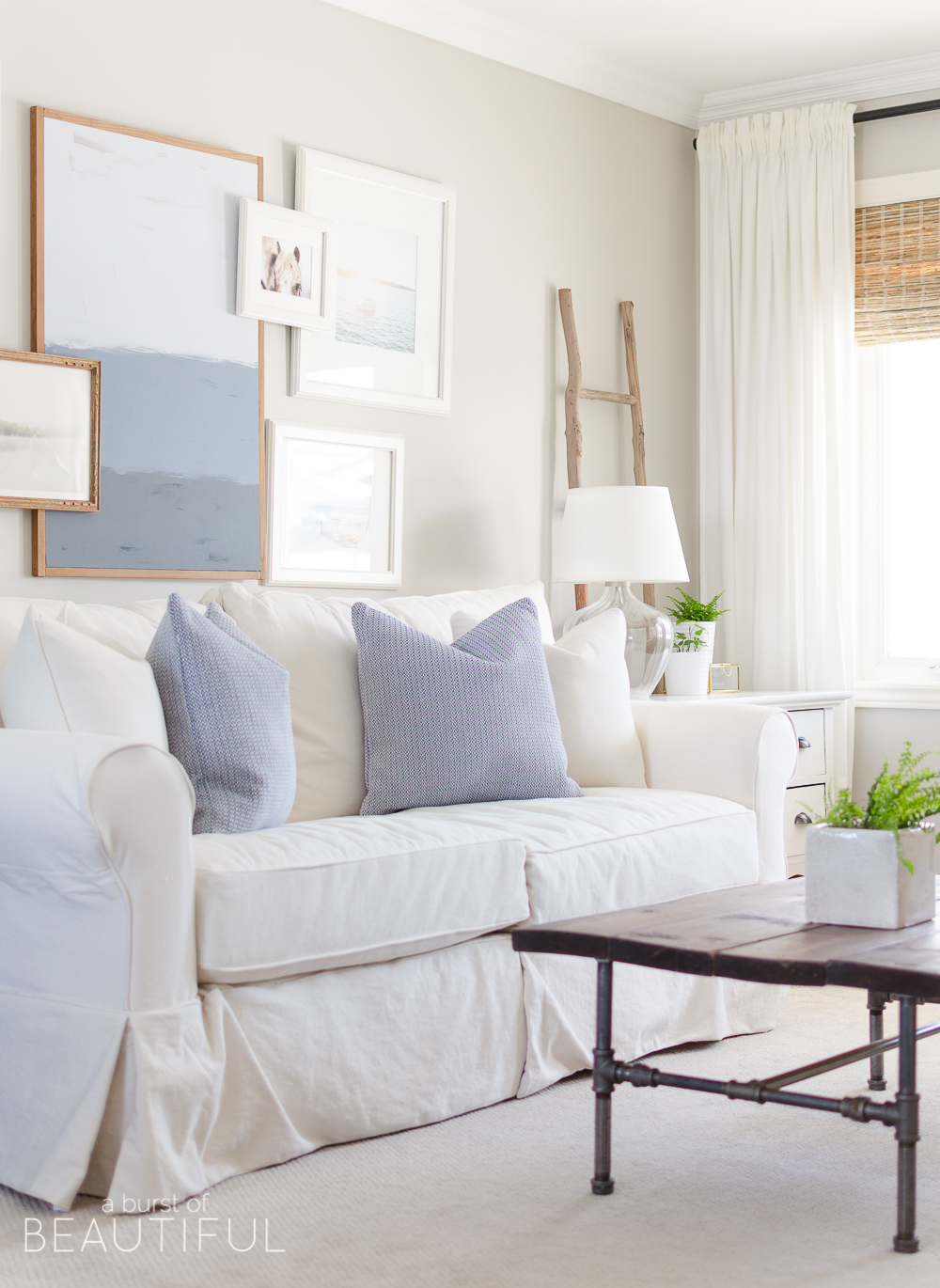 Spring Home Tour | Our Living Room - A modern farmhouse living room looks fresh and cheerful for spring with a subtle blue and white color palette and layered coastal gallery wall.