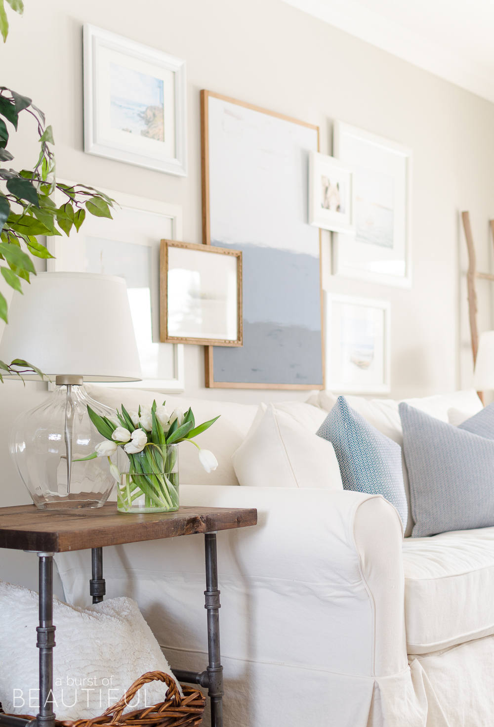 Spring Home Tour   Our Living Room - A modern farmhouse living room looks fresh and cheerful for spring with a subtle blue and white color palette and layered coastal gallery wall.