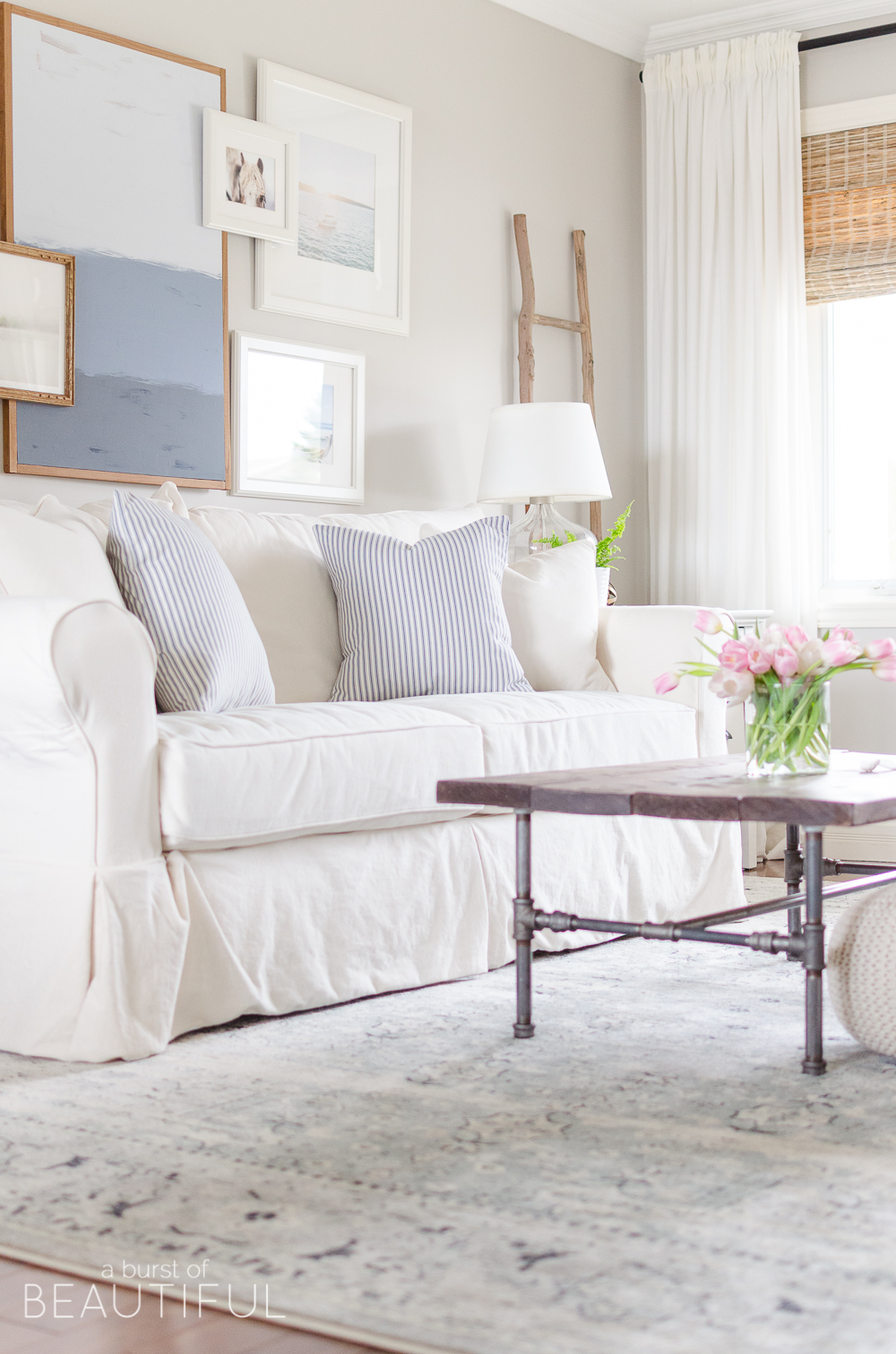 A navy blue vintage wash rug adds subtle color and pattern to this neutral modern farmhouse living room.