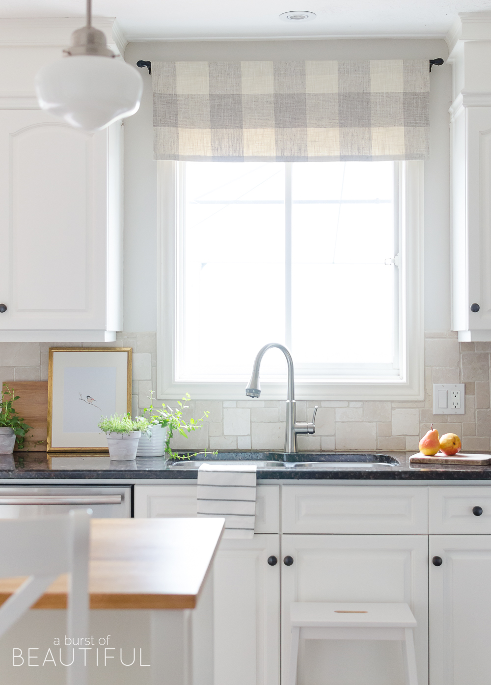 A sleek new pull-down faucet adds a touch of modern simplicity to this white modern farmhouse kitchen.