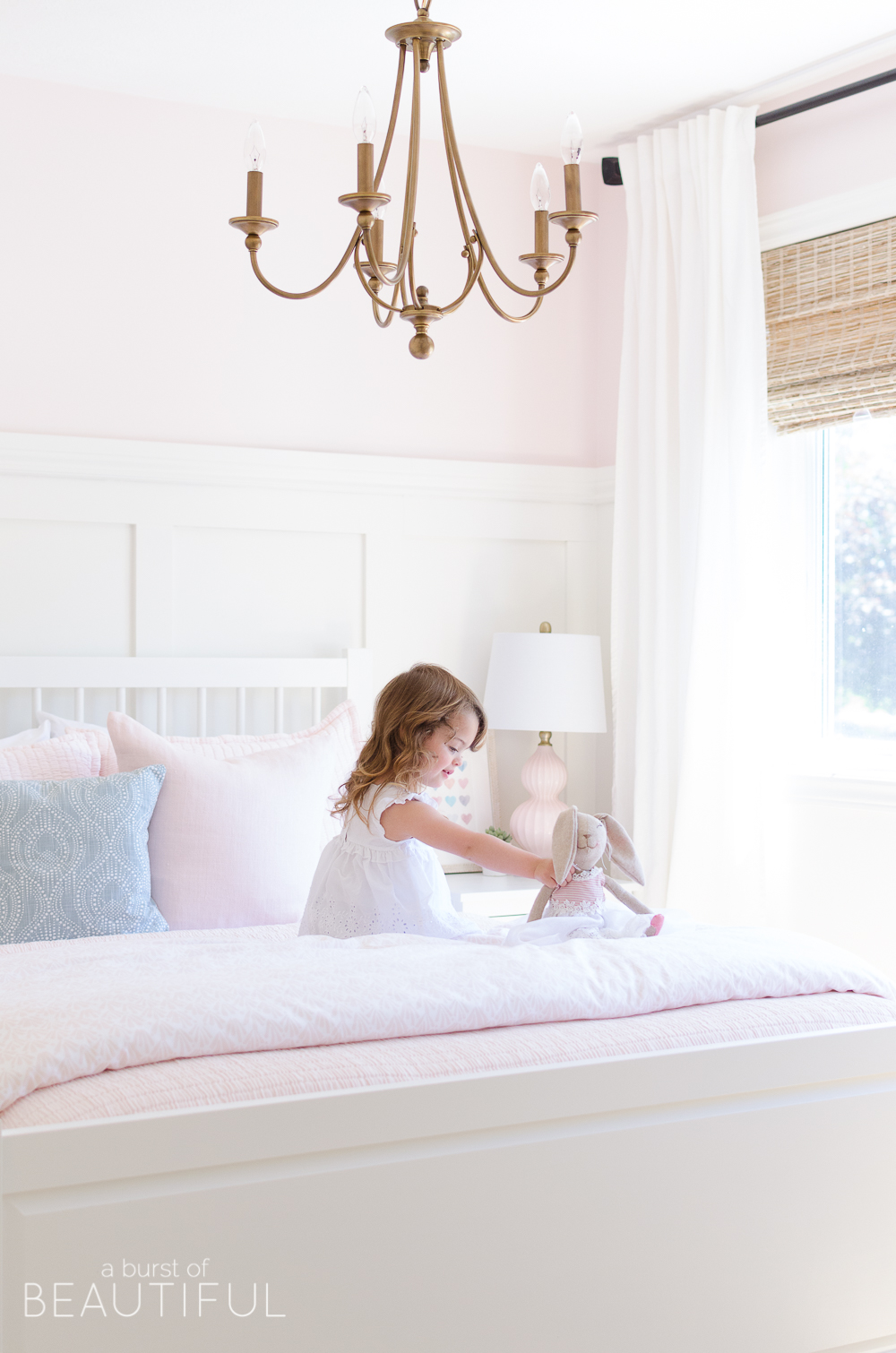 This sweet pink and white little girl's bedroom is full of soft colors and whimsical details, like board and batten, woven wood shades, a gold chandelier and pale pink bedding.