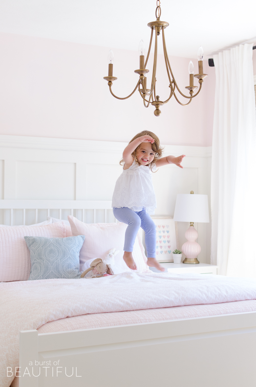 Toddler Girl Pink Bedroom Design & Decor with Chandalier jumping on bed.