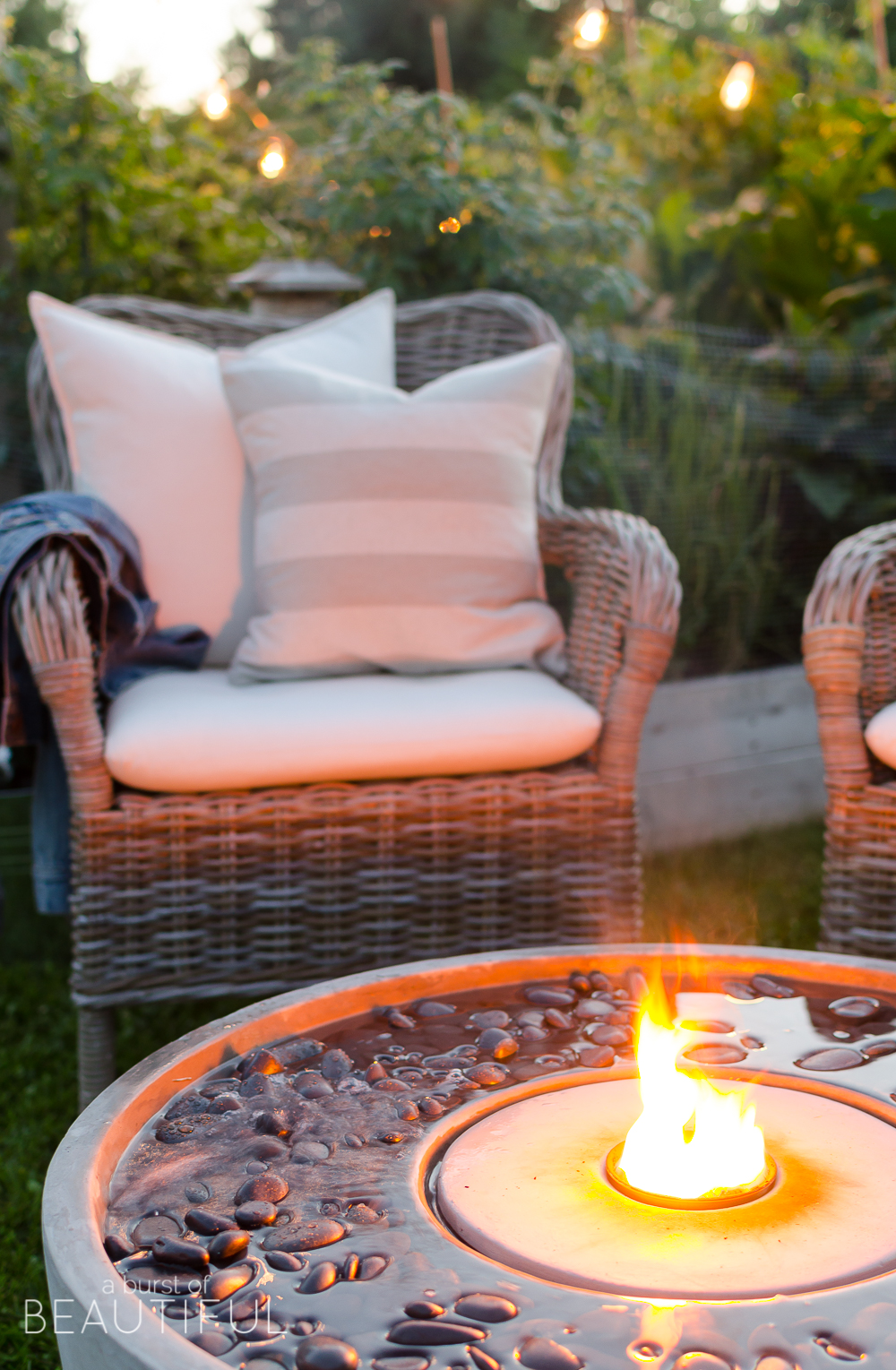 Create a cozy outdoor living space with ambiance using a fire fountain and Edison string lights.