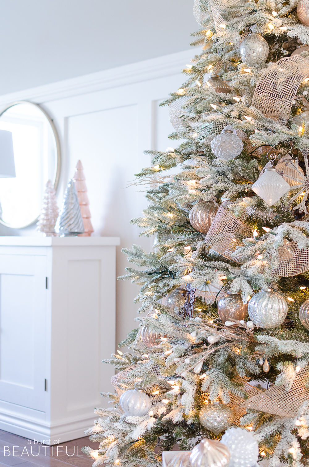 a snowy flocked christmas tree decorated in silver and rose gold adds a big dose of - Rose Gold Christmas Tree Decorations