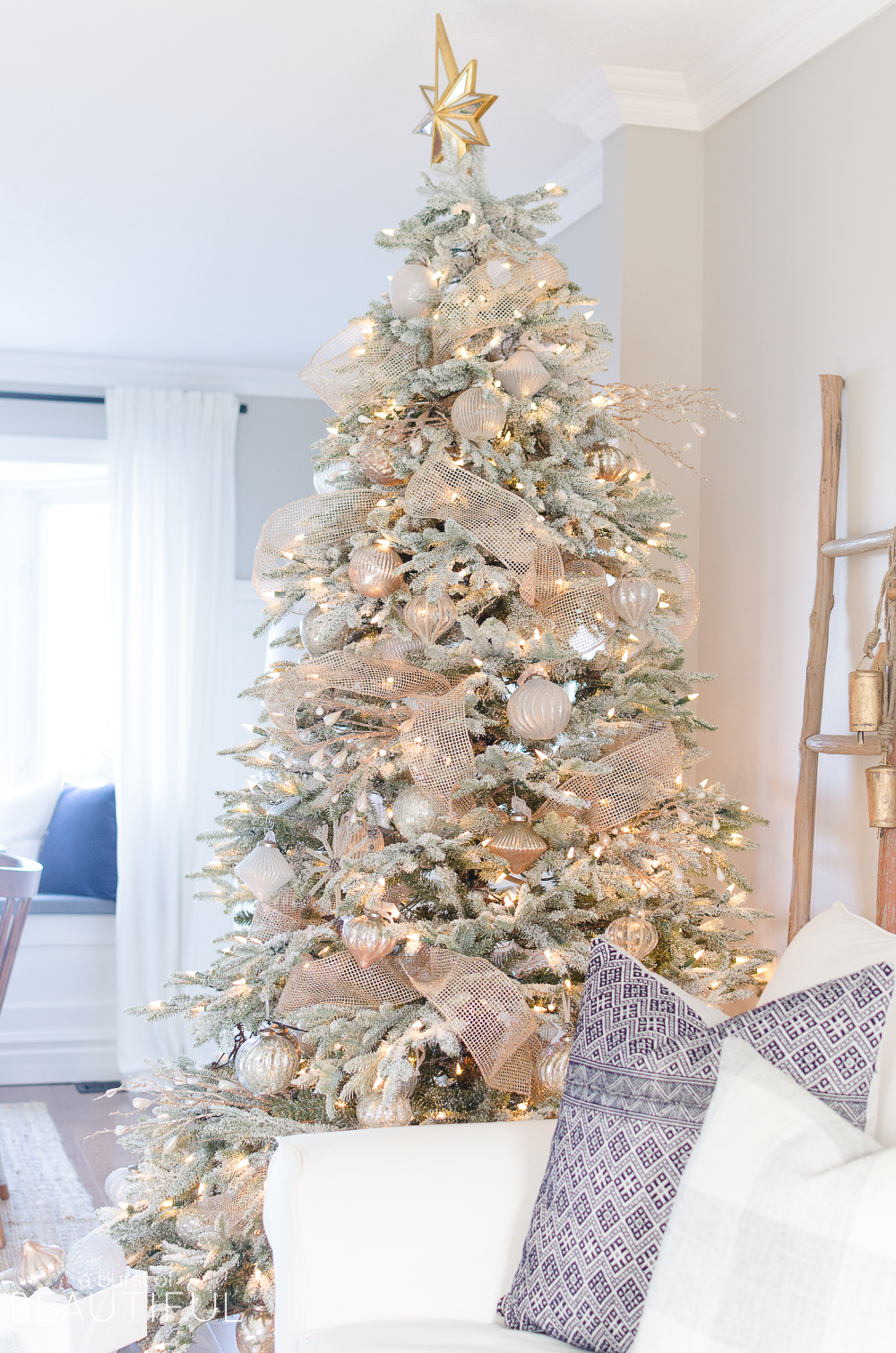a snowy flocked christmas tree decorated in silver and rose gold adds a big dose of