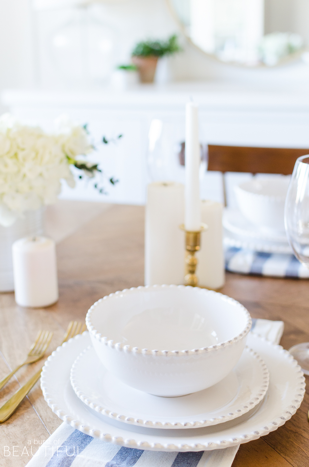A simple spring tablescape set in a classic blueand white color palette with a centerpiece of white hydrangeas and crocuses leads to easy spring entertaining.