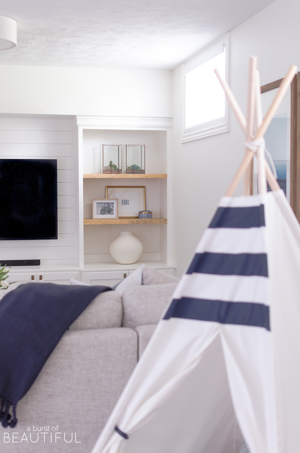 A bright family room features the perfect mix of traditional and modern design elements, including a mid-century modern sofa, open shelving and shiplap walls.
