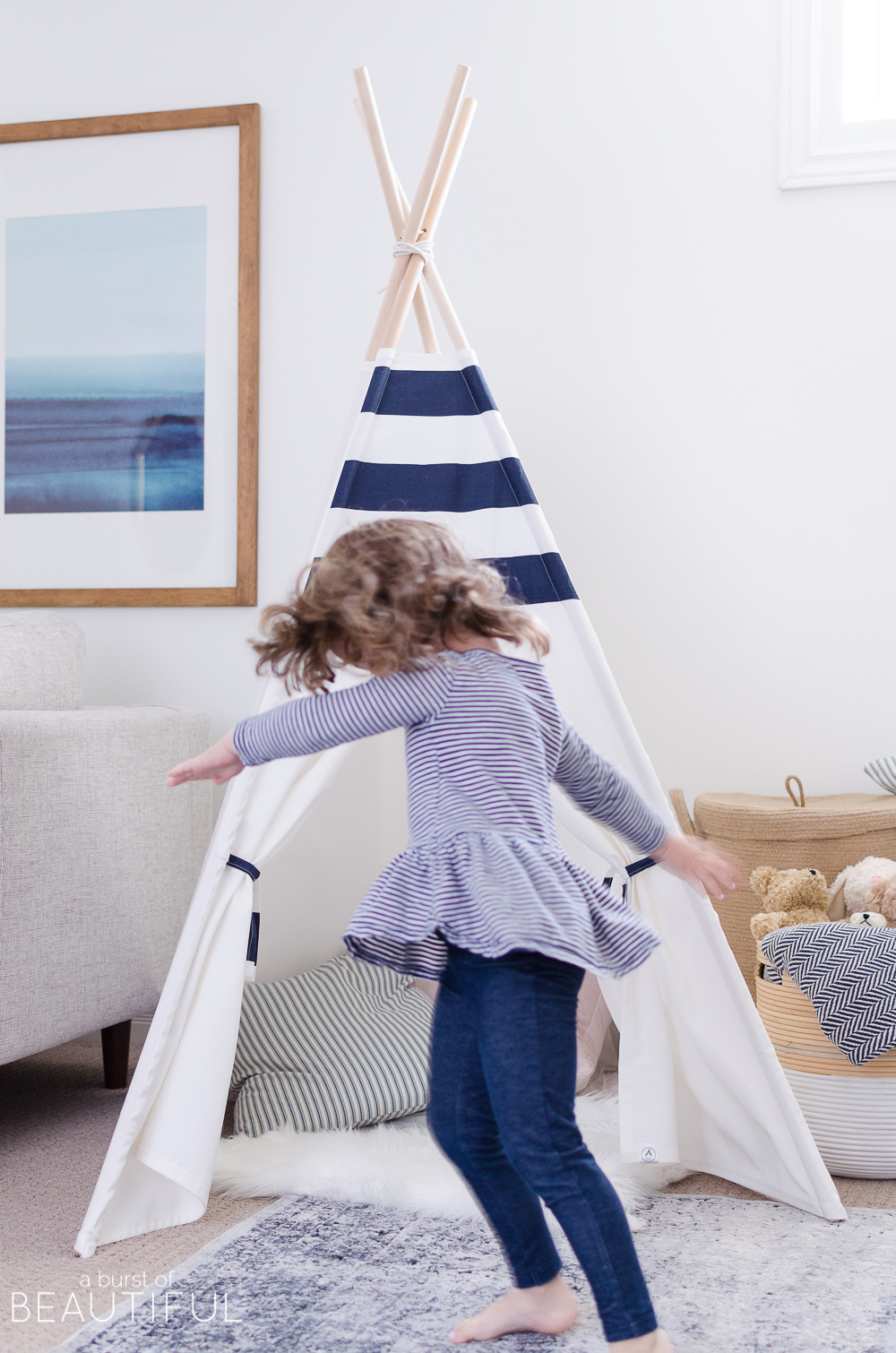 Hints of blue pop against bright white walls in this cheerful playroom, featuring a kid's desk, teepee and whimsical art.