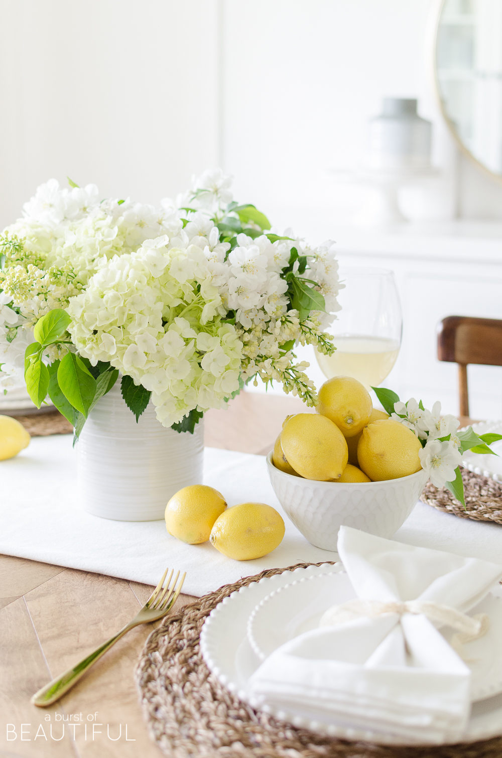Summer entertaining is easy when you set this cheerful white and yellow summer tablescape using fresh flowers and fruit.