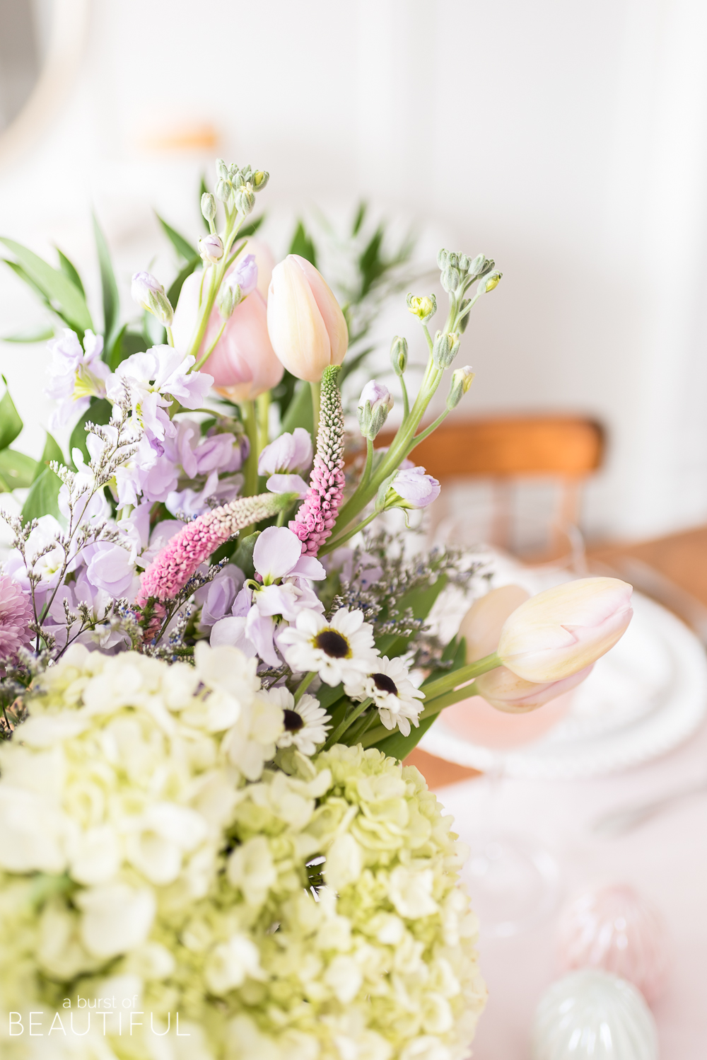 Celebrate Easter around a table set with classic white dishes, linens in pastel shades and a centerpiece full of spring blooms.