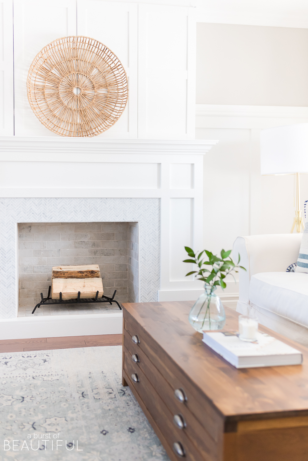 A classic craftsman style fireplace is the perfect addition to this coastal casual living room. A herringbone marble facade combined with bi-fold doors that easily open to reveal a hidden TV mix style and convenience. We are sharing the free plans here.