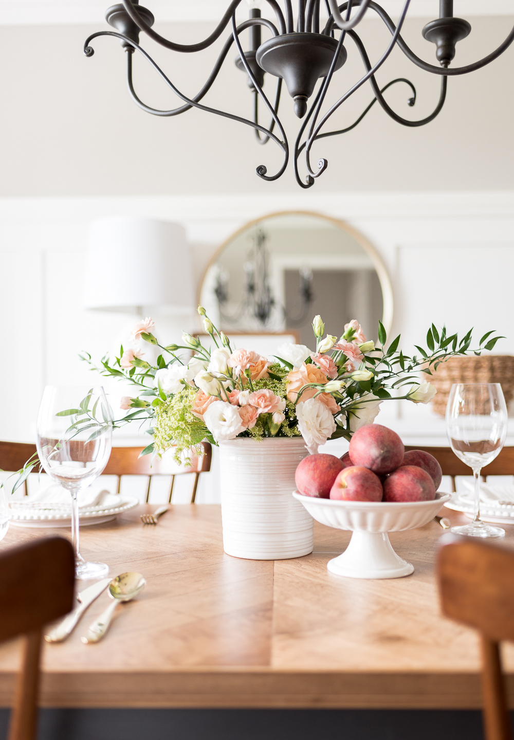 Fresh flowers in soft peach, blush and cream hues paired with a bowl of juicy peaches make an effortless centerpiece for a simple summer gathering.