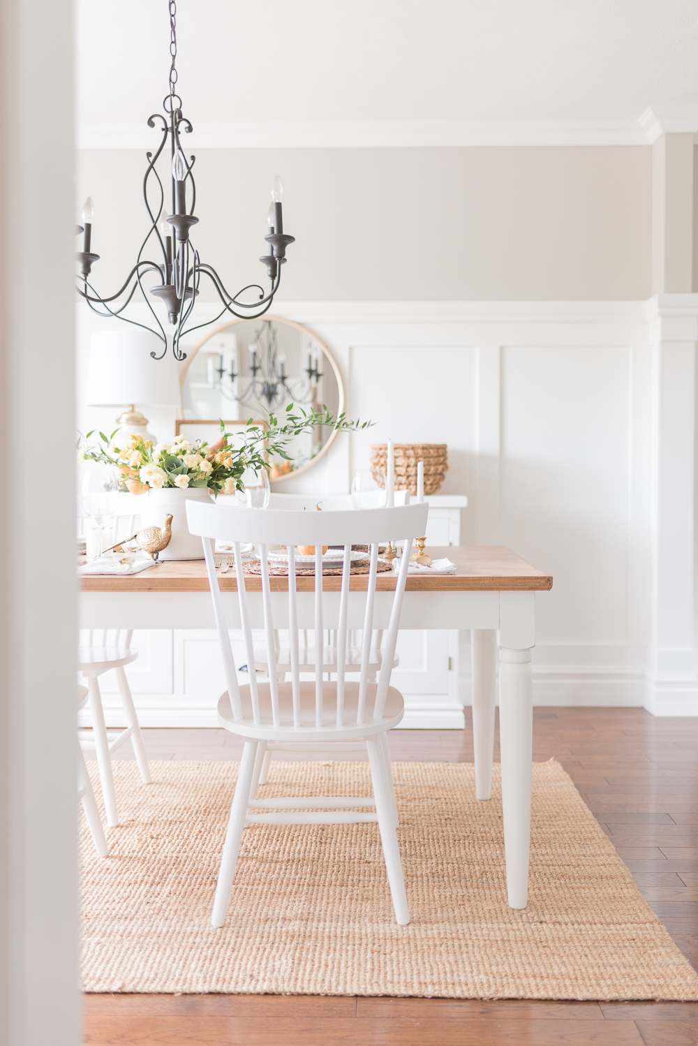 white and wood table and chairs with fall thanksgiving flower arrangement