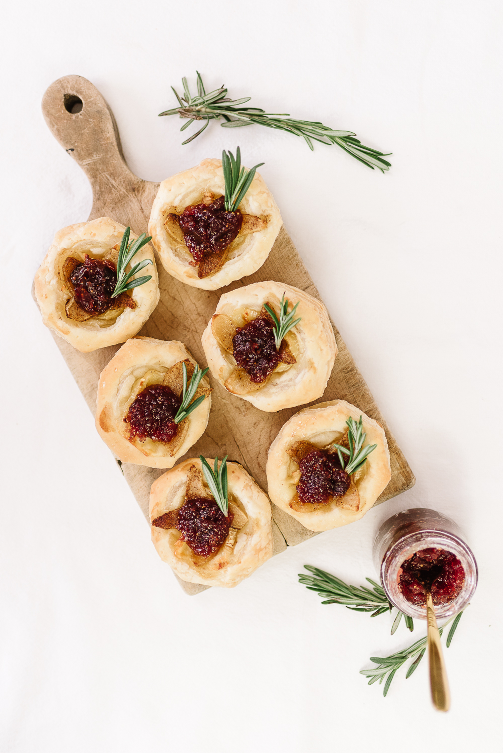 puff pastry shell brie and roasted pear tartlets on cutting board